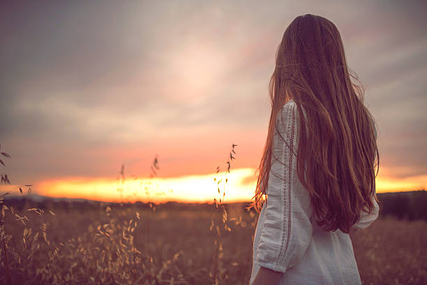 Pure Magic Rear view of a woman looking at the sunset. long hair stock pictures, royalty-free photos & images