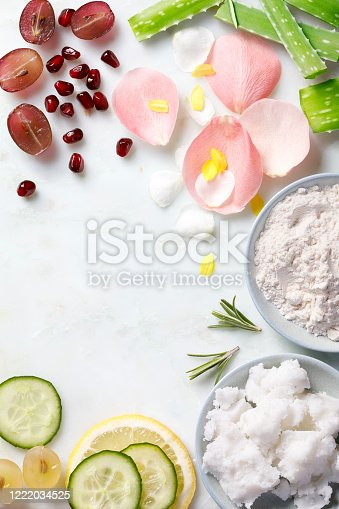 Eco friendly homemade skincare ingredients with organic fruits and flowers on marble background.