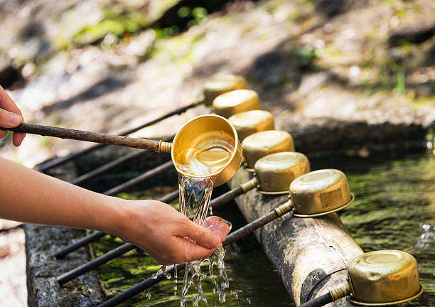 Purification at a Temizuya, part of a Japanese Shinto shrine Closeup of a woman's hands during symbolic washing and purification at a Temizuya, part of a Shinto shrine in Japan. shinto stock pictures, royalty-free photos & images