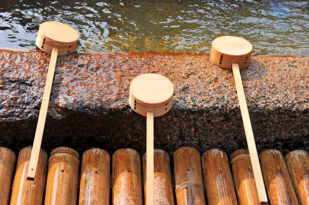 Purification fountain with bamboo and wooden scoops in Japan Purification fountain with bamboo and wooden scoops at a shintu shrine in Japan. shinto shrine stock pictures, royalty-free photos & images