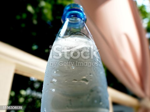 A bottle of purified water on the table in sidewalk cafe
