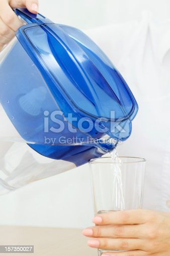 Close-up of female hands pouring filtered water into the glass. Shallow dof.