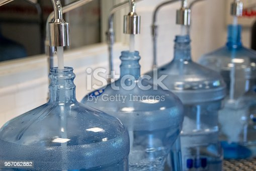 Big five gallon plastic containers being filled of purified water