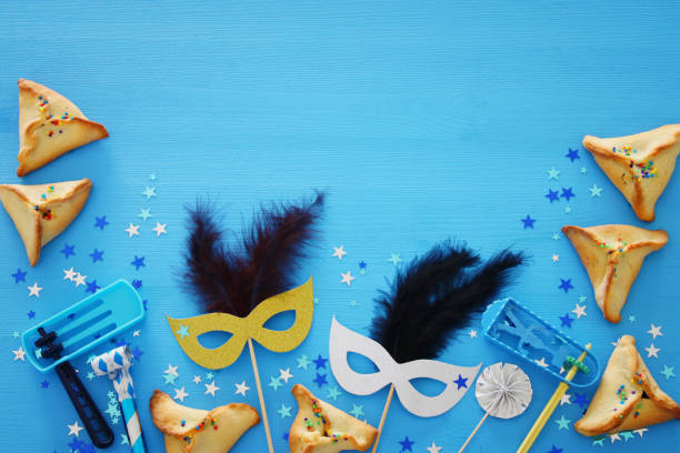 Purim celebration concept (jewish carnival holiday) over blue wooden background. Top view. – zdjęcie