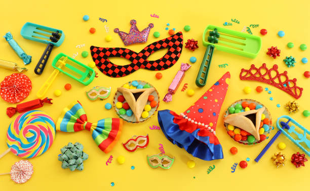 Purim celebration concept (jewish carnival holiday) over yellow background. Top view, flat lay stock photo