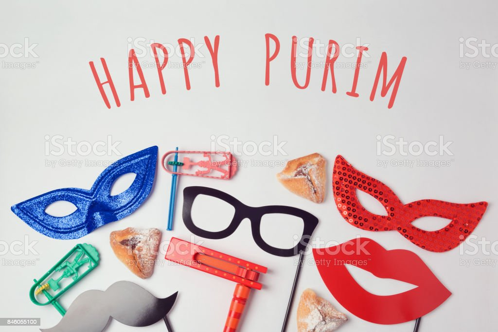 Purim celebration concept with carnival mask and photo props on white background. Top view from above stock photo
