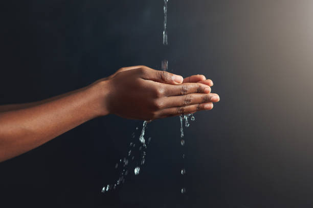 Purity in the palm of your hands Cropped shot of hands held out under a stream of water against a grey background hands cupped stock pictures, royalty-free photos & images