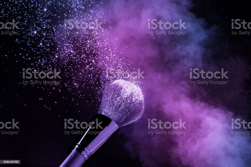 purple and glittering blusher explosion isolated on black background stock photo
