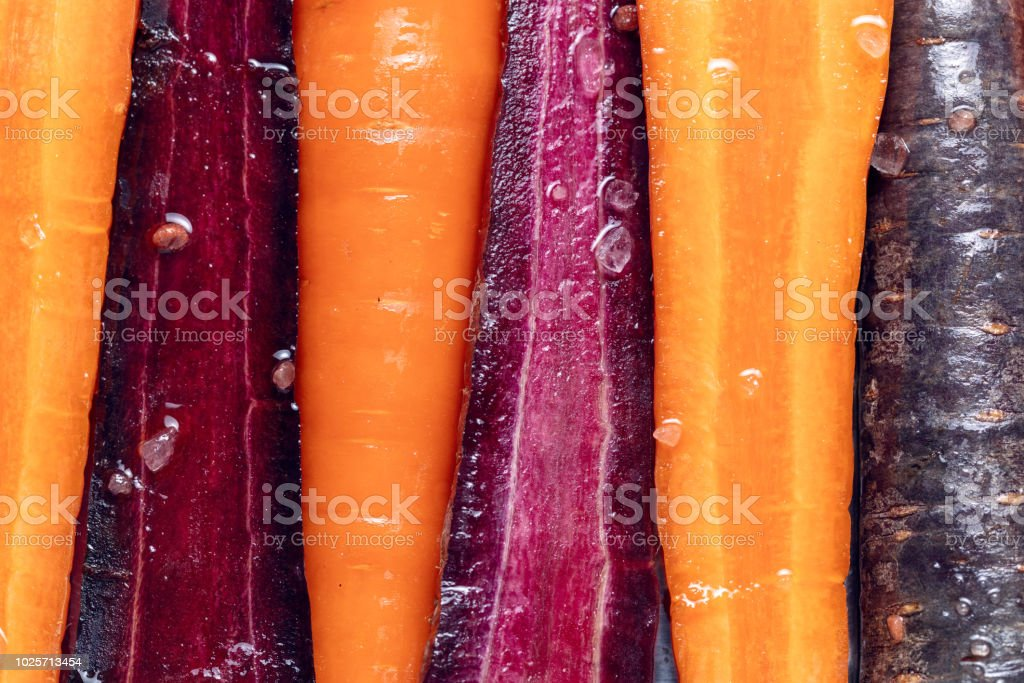 Purple and orange carrot, ready to roast, close up, flat lay.