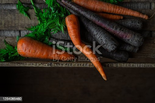Purple and orange carrots in wooden crate, closeup view. Horizontal orientation
