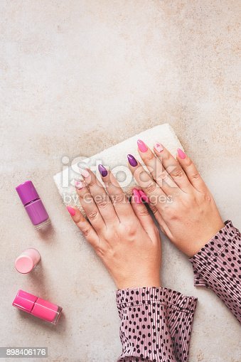 1147741037istockphoto Purple and pink manicure on female hands 898406176