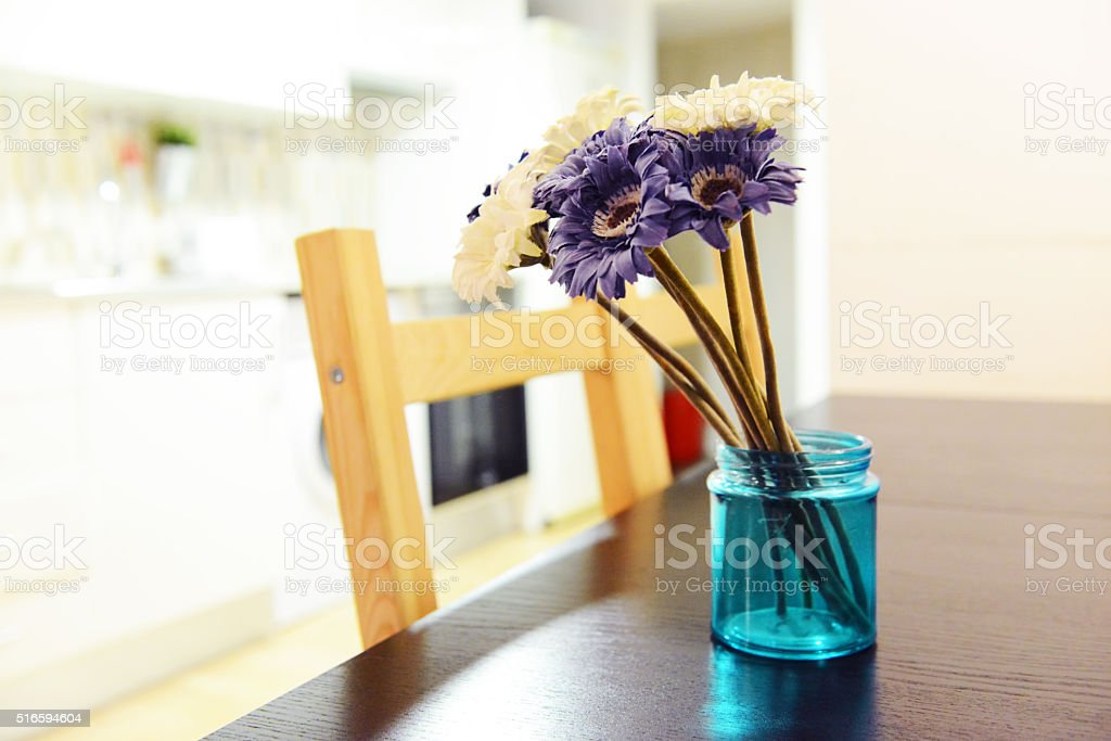 Purple and white gerberas bouquet in a blue vase stock photo