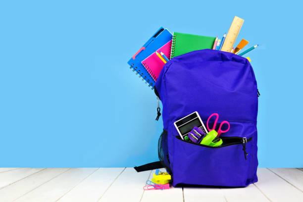 紫色背包裡裝滿了藍色背景的學校用品。回學校去 - 背囊 個照片及圖片檔