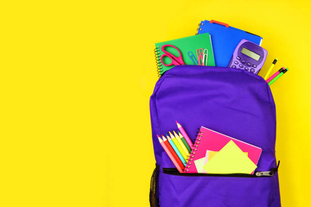 Purple backpack full of school supplies against a yellow background, top view with copy space stock photo