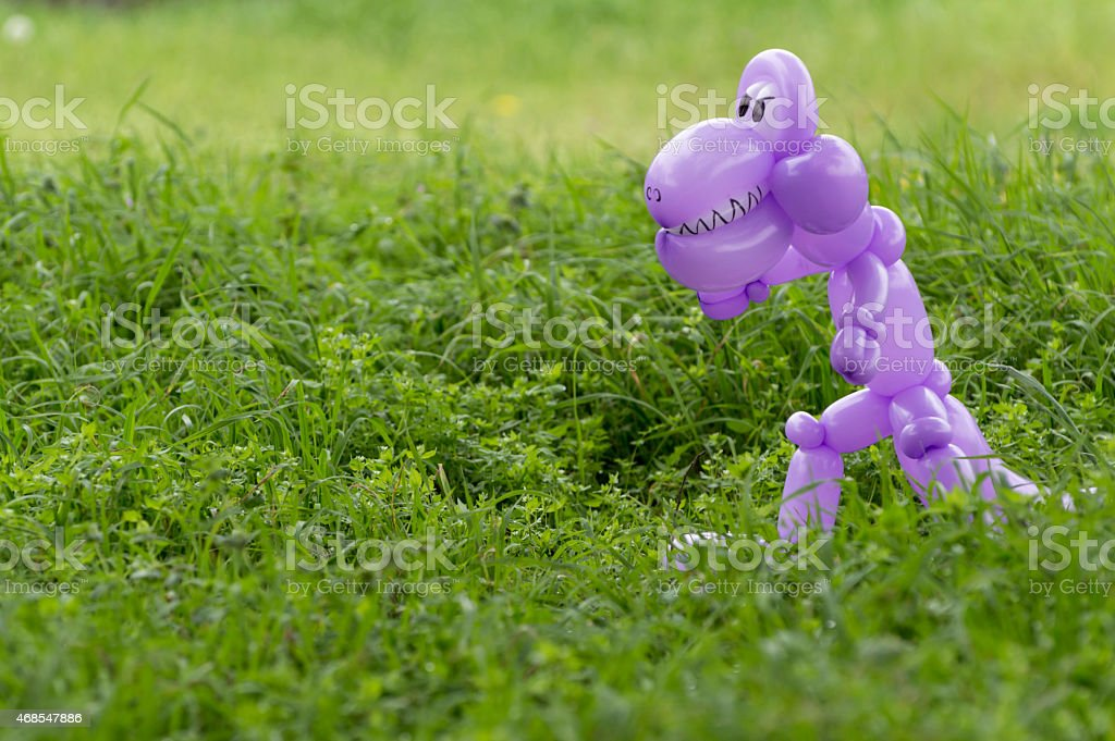 Purple balloon animal dinosaur in green grass of back yard stock photo