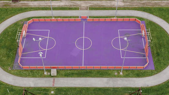 A purple coloured basketball and soccer field