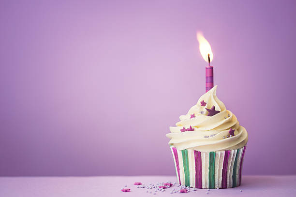 Purple birthday cupcake Purple birthday cupcake with copyspace to side first birthday stock pictures, royalty-free photos & images