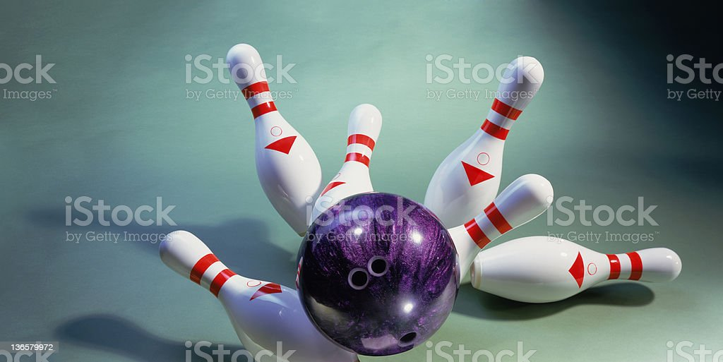 A purple bowling ball knocking over pins stock photo