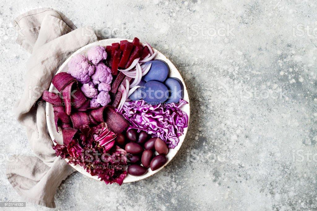 Bol de Bouddha pourpre avec des carottes en spirale, chou-fleur, betterave, oignon, pomme de terre, chou rouge râpé, salade de radicchio, olives kalamata. Bol de légumes détox végétalien - Photo