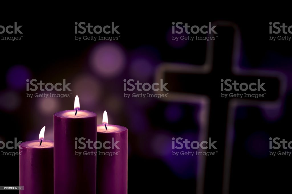 Purple candles with a cross symbol stock photo