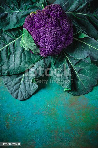 Purple cauliflower raw with plant leaves on green background