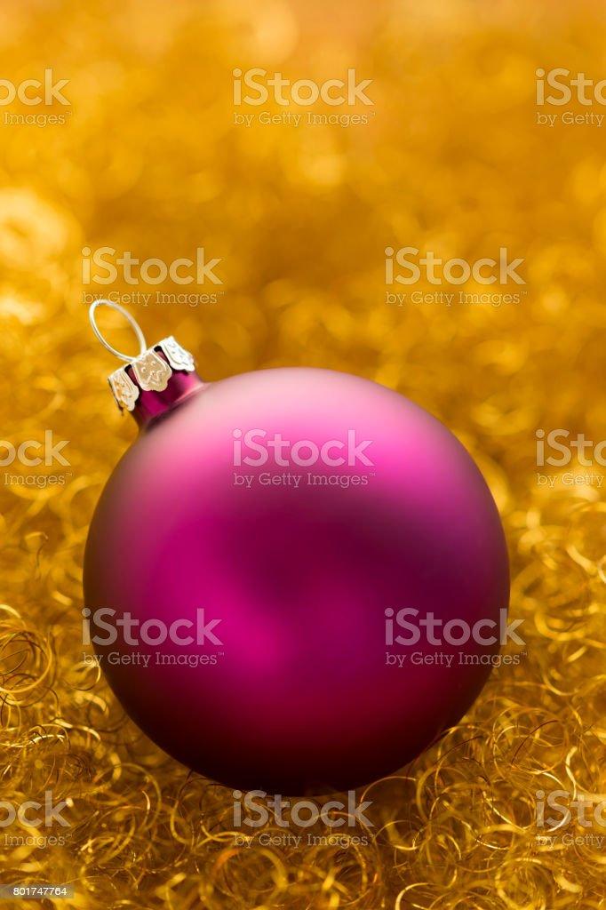 Purple christmas ball on gold glitter stock photo