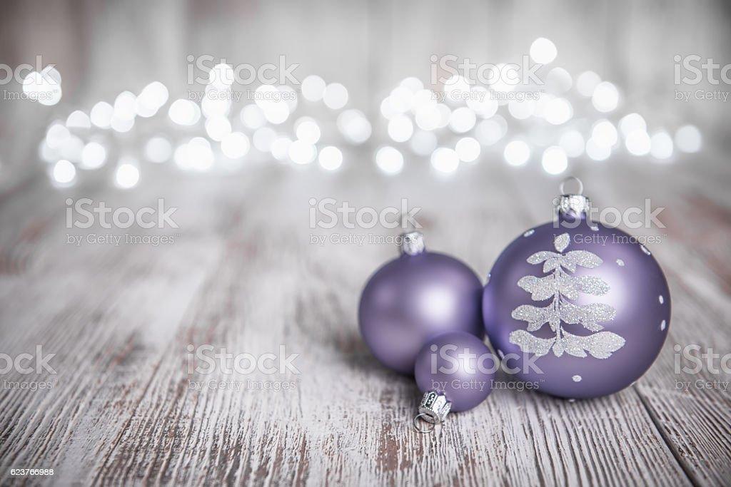 Purple Christmas Ornaments on Rustic Wood Board and defocused lights stock photo