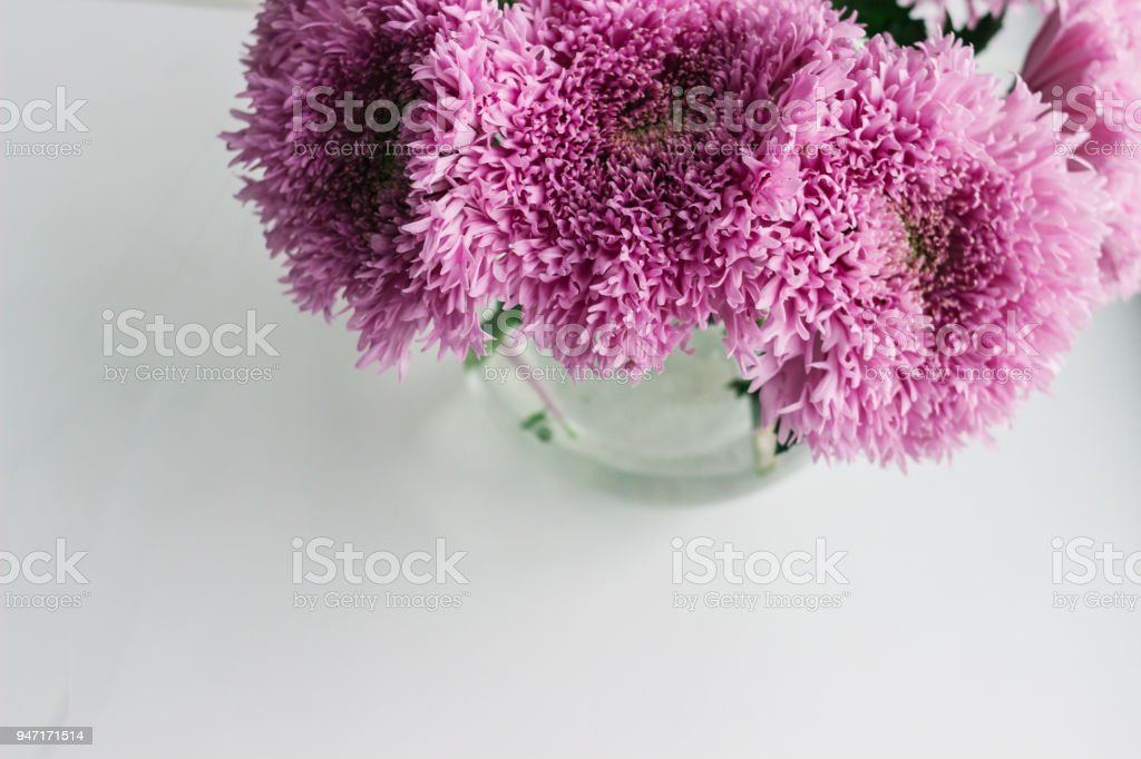 Pink chrysanthemum in glass vase on the wooden table