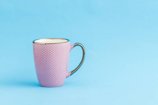 lila kaffeebecher auf blauem hintergrund mit textfreiraum - küche deko lila stock-fotos und bilder