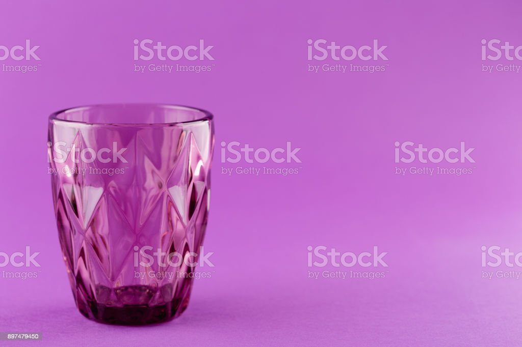 Empty drinking glass purple cup on magenta background with copy space