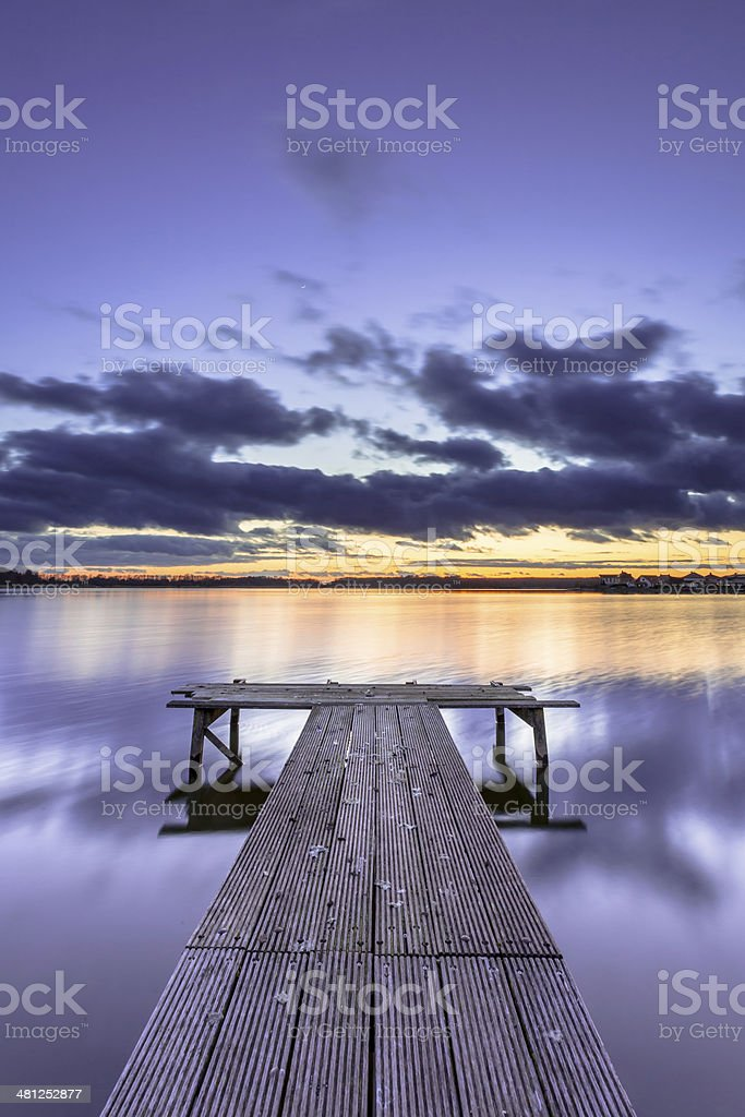 Purple Colored Sunset over Tranquil Lake with Wooden Jetty stock photo