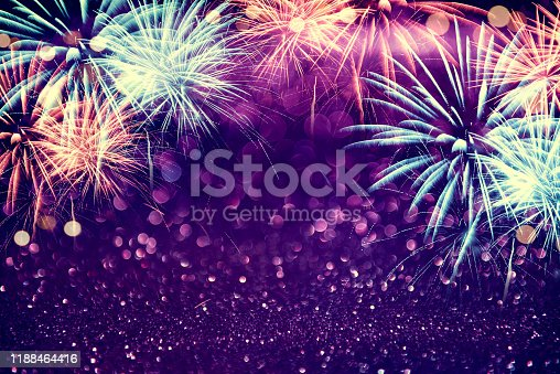 969086552istockphoto Purple colorful fireworks and bokeh in New Year eve and copy space. Abstract background holiday. 1188464416