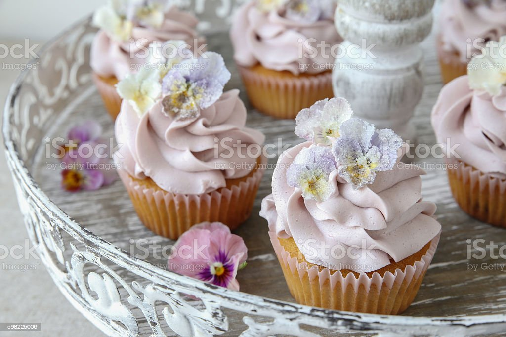 Purple cupcakes with sugared edible flowers on vintage cake stan foto royalty-free