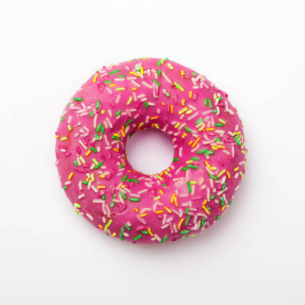 purple donut in glaze on a white background. great fresh tasty purple donut drizzled with glaze - bombolone foto e immagini stock