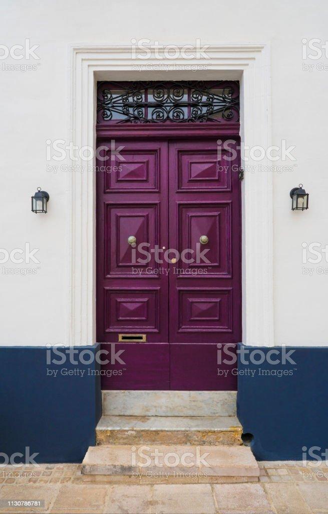 Purple door on the white, blue wall and lamp. Maltese door in Birgu city. Malta. Europe stock photo