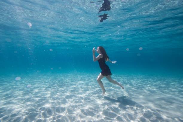 lila gekleidete junge frau im wasser schwimmen - meerjungfrau kleid stock-fotos und bilder