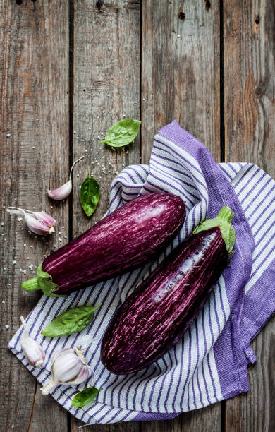 purple eggplant (aubergine), garlic and basil leaves on vintage wooden table - melanzane foto e immagini stock