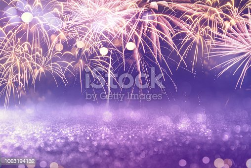 969086552istockphoto Purple fireworks and bokeh in New Year eve and copy space. Abstract background holiday. 1063194132