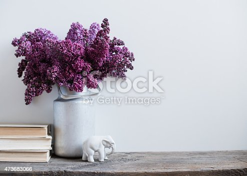 istock Purple flowers in a vintage milk tin with porcelain elephant 473683066