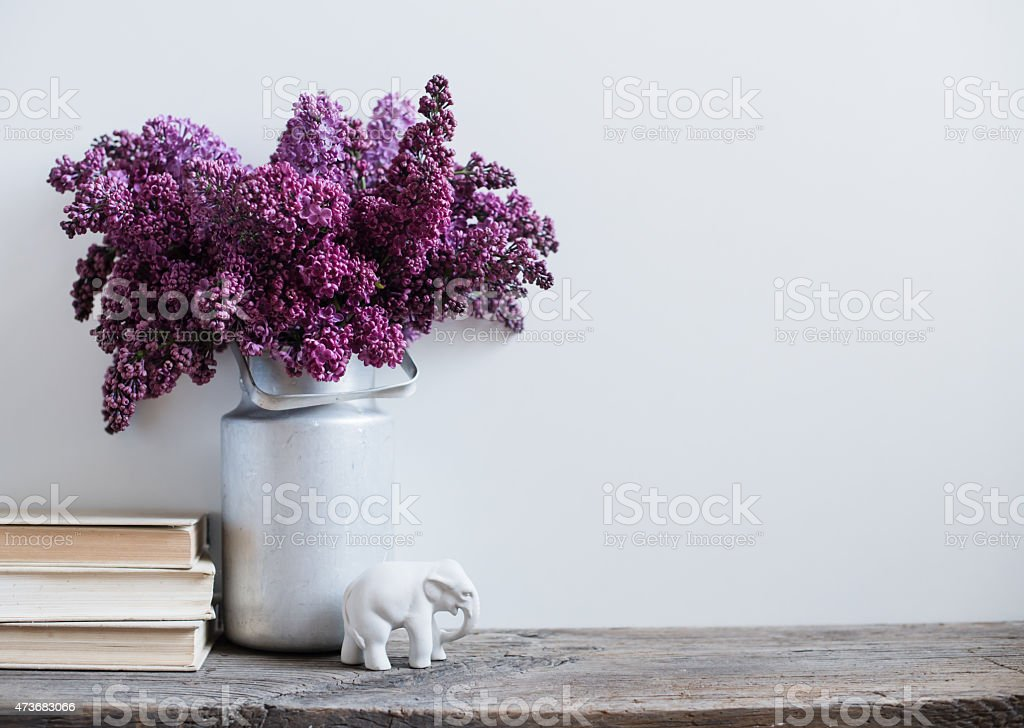 Purple flowers in a vintage milk tin with porcelain elephant stock photo