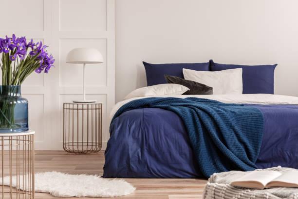 lila blumen in blauer glasvase auf stilvollem tisch im weißen schlafzimmer-interieur mit komfortablem bett - marineblau schlafzimmer stock-fotos und bilder