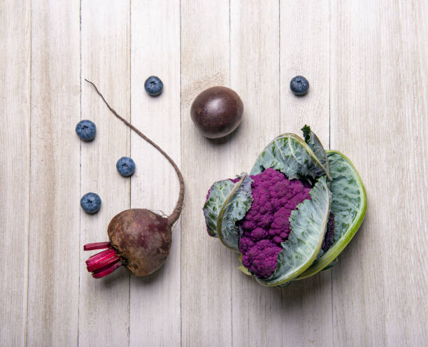 Purple fruits and vegetables over wood background stock photo