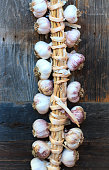 A white and purple garlic braid hangs on an old weathered wooden plank. Copy space available.