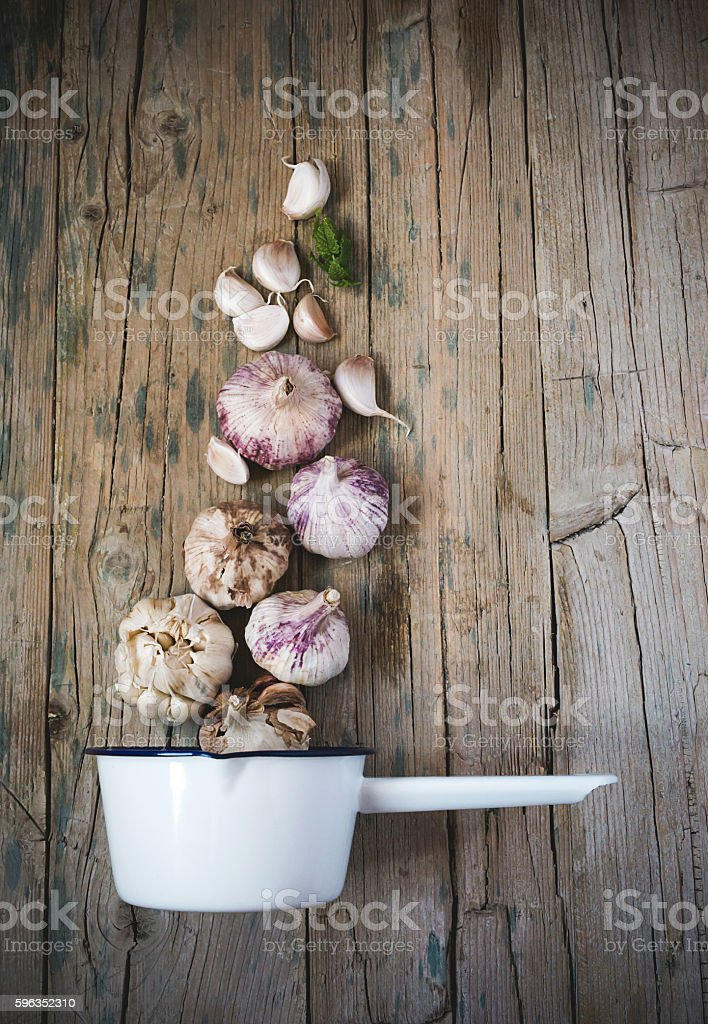Purple garlics on a napkin on a wooden rustic table royalty-free stock photo