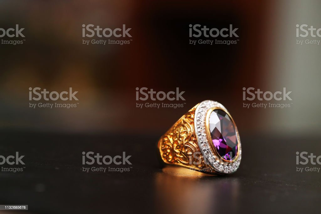 Purple gem stone on gold ring with diamond