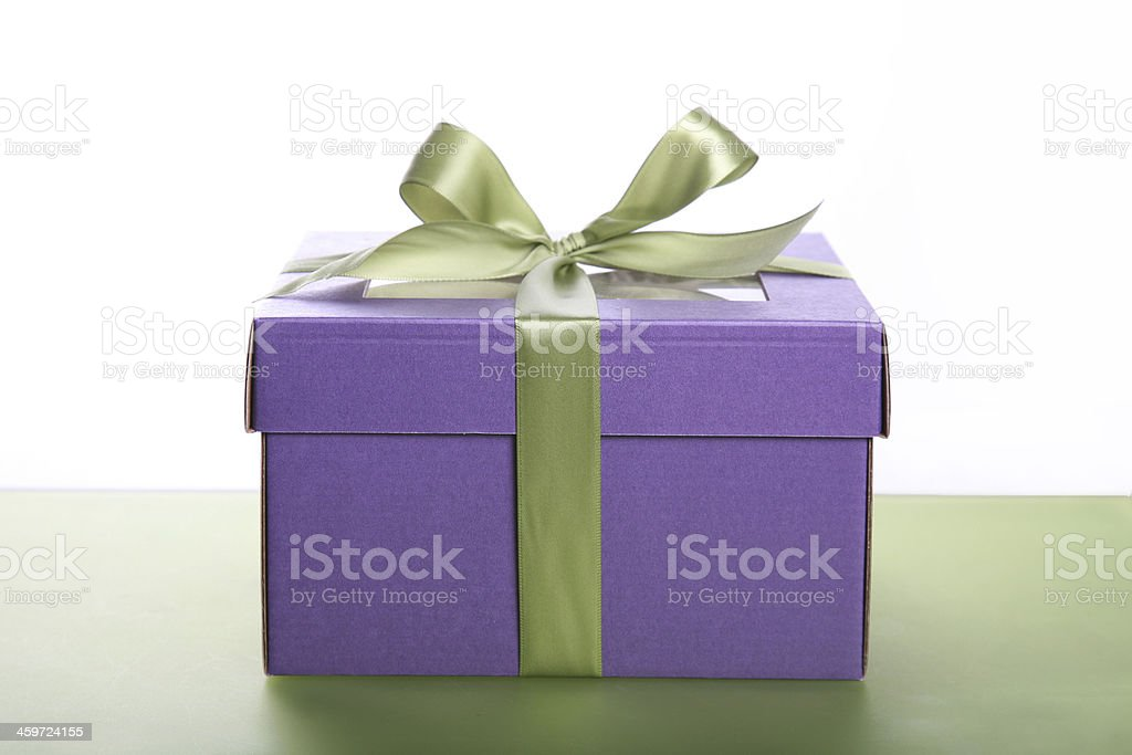Purple gift box with green satin ribbon side view stock photo