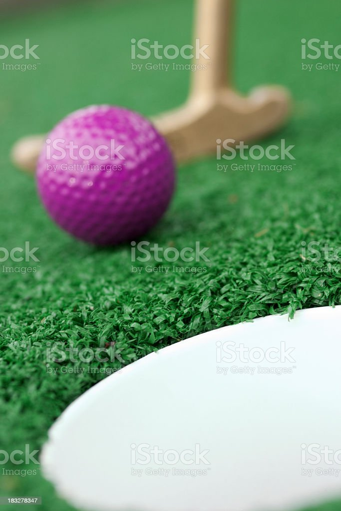 Purple golf ball being putted for miniature golf royalty-free stock photo