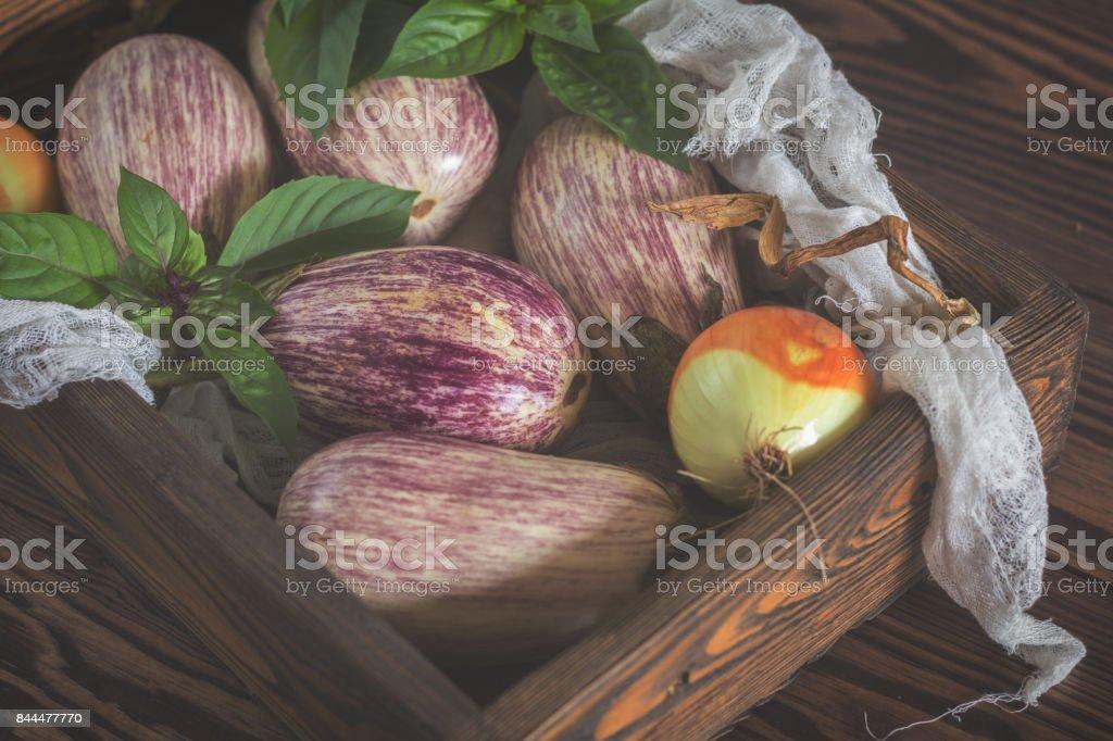 Purple graffiti eggplants, onion and basil. Toned royalty-free stock photo
