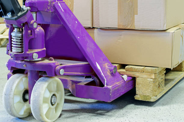 Purple hand pallet truck Purple hand pallet truck with cardboard boxes close up. pallet jack stock pictures, royalty-free photos & images