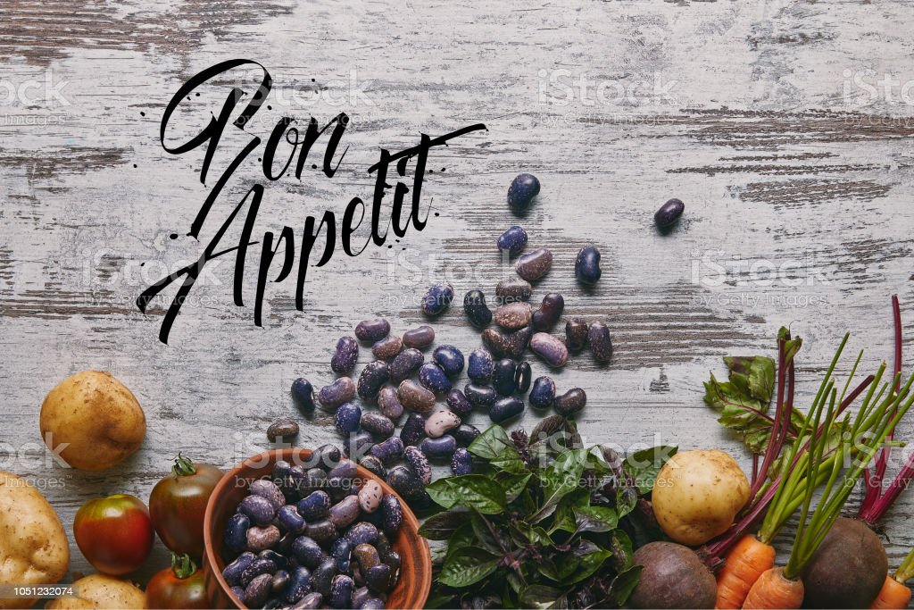 Purple haricot beans and raw vegetables for cooking on rustic wooden table with 'bon appetit' lettering stock photo